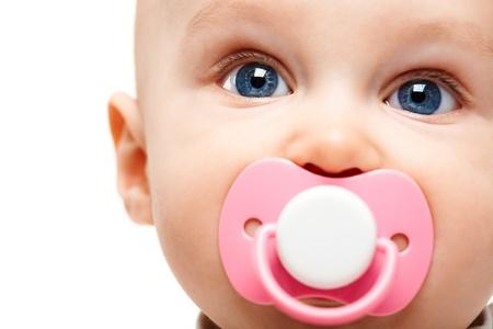Cara de bebé adorable con chupete en la boca mirando cámara