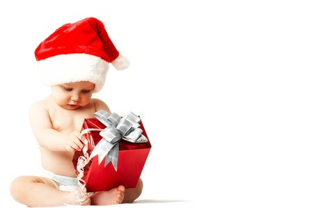 baby christmas: Curious and surprised baby in Santa cap looking at giftbox in his hands Stock Photo
