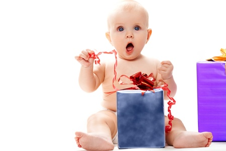 Surprised baby sitting with big giftbox by her side over white background photo