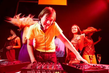 Portrait of handsome deejay looking at camera with dancing teens on background photo