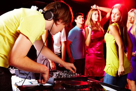 Smart deejay adjusting technics with dancing teens on background Stock Photo - 8528123