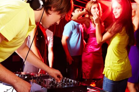 Smart deejay adjusting technics with dancing teens on background photo