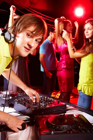 Smart deejay looking at camera with dancing teens on background photo