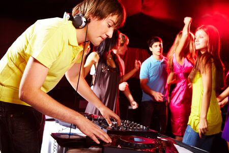 dj boy: Smart deejay spinning turntables with dancing teens on background