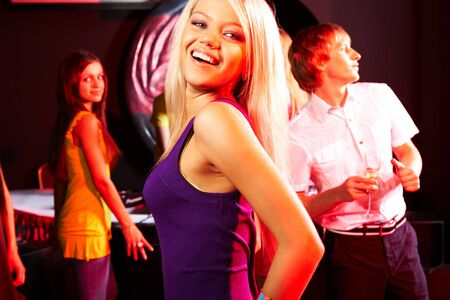 Image of energetic girl looking at camera while dancing on background of her friends photo