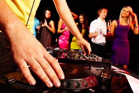 turntable: Close-up of human hand spinning turntable with group of dancers on background Stock Photo