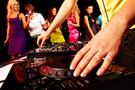 dj: Close-up of human hand spinning turntable with group of dancers on background Stock Photo