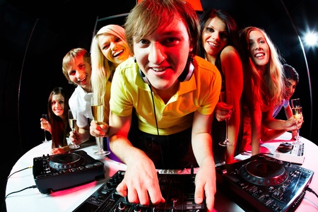 dj boy: Portrait of handsome deejay looking at camera with happy teens behind