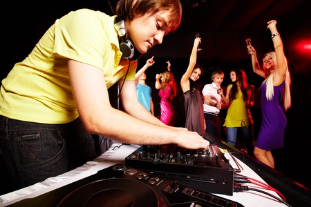 Smart deejay working at disco with dancing teens on background photo