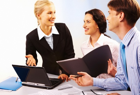 Business lady by the laptop pointing at its monitor and looking at her co-workers with smile photo