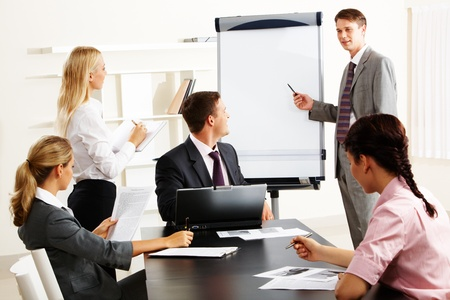 business workshop: Image of smart business people looking at their leader while he explaining something on whiteboard during seminar