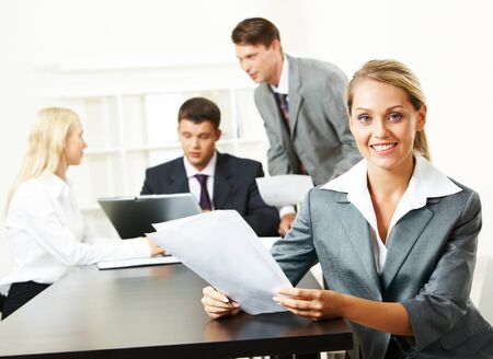 attractive secretary holding paper and looking at camera during business conversation  photo