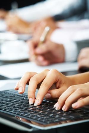 Vrouwelijke handen aanraken van de sleutels van de laptop tijdens een briefing over de achtergrond van menselijke handen