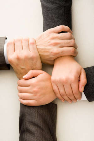 altogether: Image of crossed hands over workplace  Stock Photo