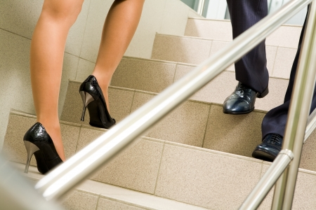 office shoes: Image of female and male legs going along marble ladder in office building