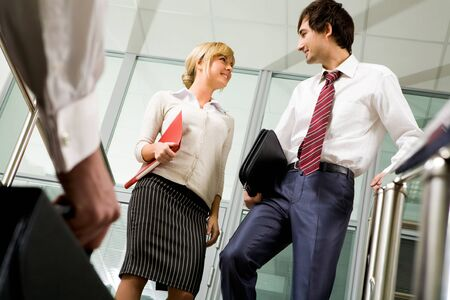Successful business partners communicating in office building photo
