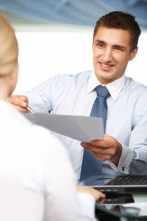 agente comercial: Empleador guapo dando el contrato a su compa�ero para firmar Foto de archivo