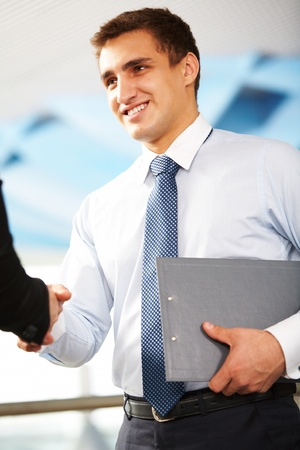 PARTNER: Confident businessman handshaking with partner after signing contract