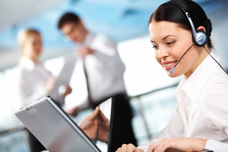 Portrait of executive female in headset working on background of communicating partners photo