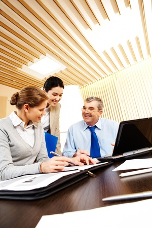 old business man: Friendly business group sitting at the desk in the office and planning work