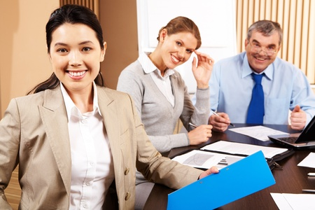 asian working woman: Image of attractive female on background of smart co-workers