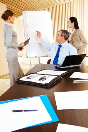 Successful man pointing at whiteboard with two businesswomen standing near by photo
