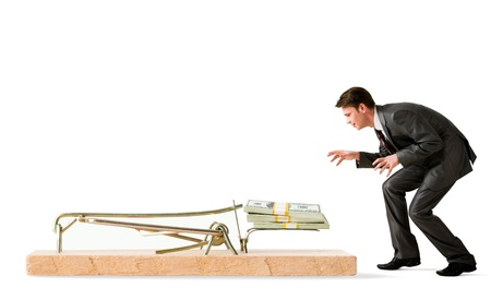 money risk: attentive businessman standing by mouse trap and looking at money
