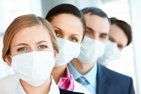 health care protection: Pretty female in protective mask looking at camera with row of partners behind