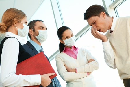 epidemic: Group of co-workers in protective masks looking strictly at sneezing man Stock Photo
