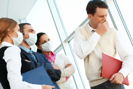 epidemic: Group of associates in protective masks looking strictly at coughing man Stock Photo