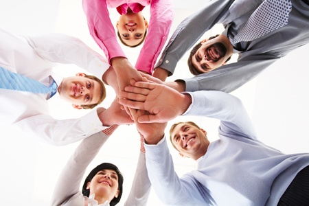 shake hands: Below shot of smiling co-workers making pile of hands