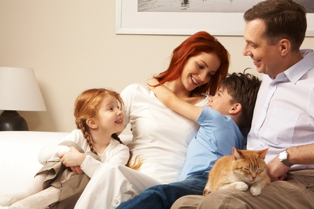 Photo of cute boy embracing his pretty mother surrounded by playful daughter and their father photo