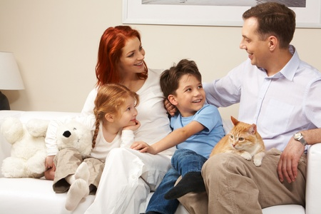 Curious children and woman looking attentively at handsome man while relaxing on sofa photo