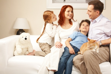 Friendly family members sitting on comfortable sofa and communicating at home photo