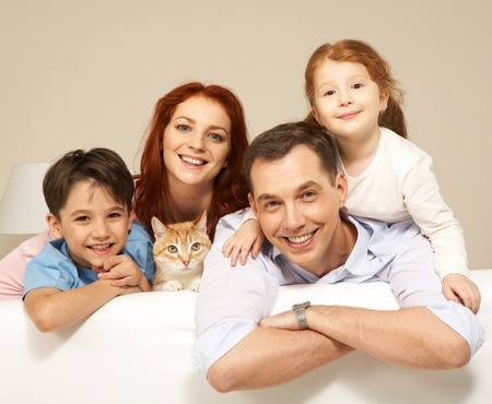sister: Portrait of siblings and their parents with cute cat looking at camera