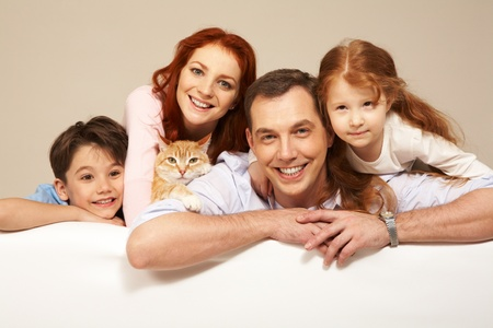 Happy couple and their two children smiling with pet among them photo