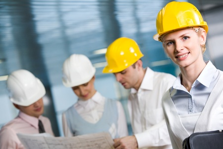 work environment: Portrait of confident woman in helmet looking at camera in working environment Stock Photo