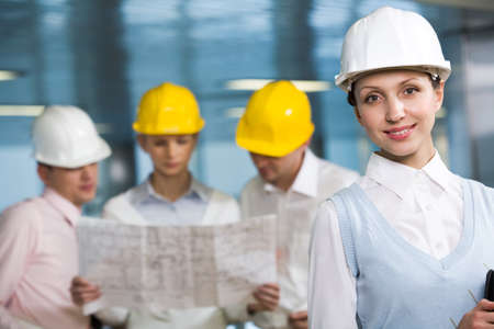 Portrait of confident woman in helmet looking at camera in working environment photo