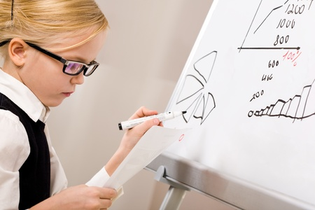 Portrait of smart girl with pen in hand standing by whiteboard photo