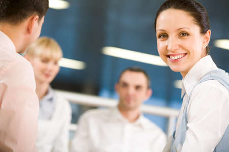 Portrait of happy businesswoman smiling at camera on background of working employees photo