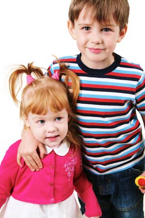 Portrait of smiling boy looking at camera while embracing his sister photo