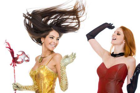 Photo of joyful actresses in fashionable dresses laughing over white background photo