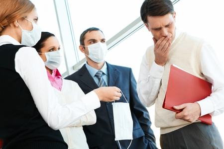 discontent: Group of associates in protective masks giving one to sick man Stock Photo