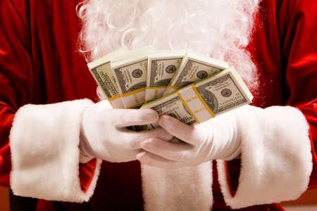 Close-up of Santa�s hands with stacks of dollar banknotes photo