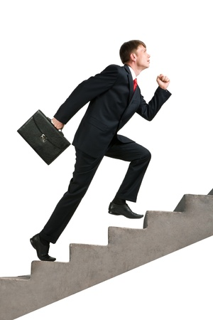 Image of confident businessman with briefcase walking upstairs photo