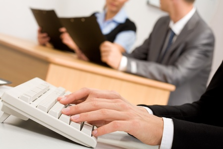 hands pushing buttons of computer keyboard with communicating partners on background photo