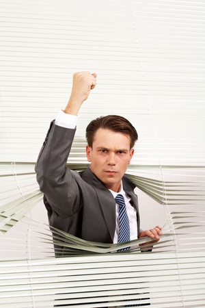 Portrait of angry man looking at camera out of venetian blind and showing fist Stock Photo - 9164316