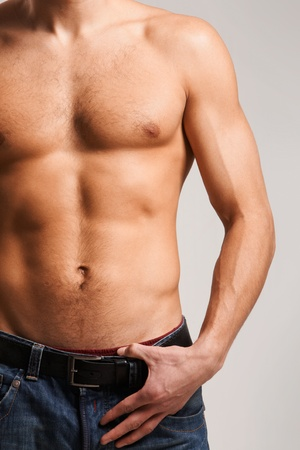 Torso of strong man wearing jeans in isolation photo