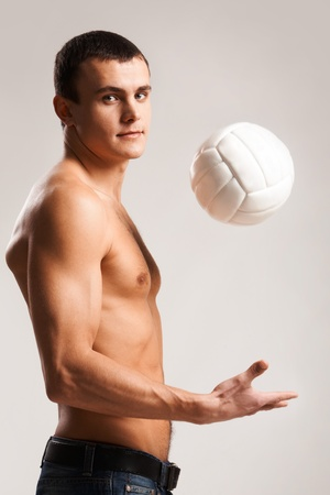 Photo of shirtless man playing with volley ball and looking at camera photo