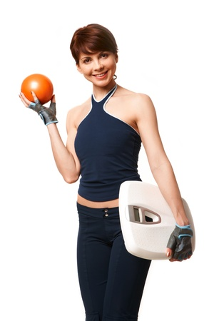 Portrait of sporty woman with ball and scales in hands looking at camera photo